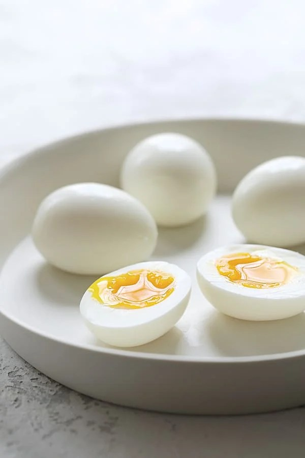 Arugula, Egg and Asparagus Salad with Creamy Lemon Vinaigrette - Shot of cooked eggs with runny yolk in white dish
