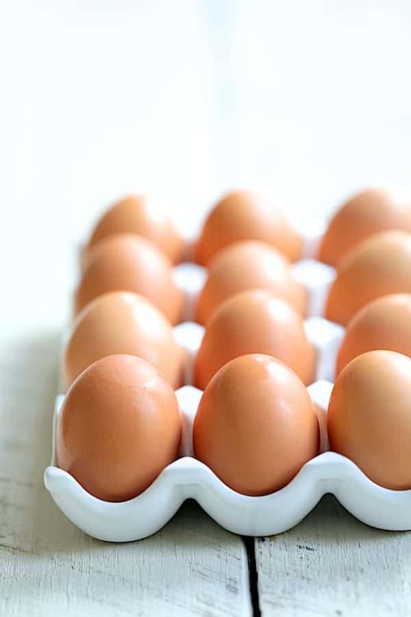Arugula, Egg and Asparagus Salad with Creamy Lemon Vinaigrette - Straight-on shot of brown eggs in ceramic egg holder