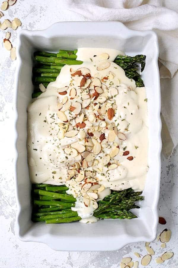 Chicken Asparagus Divan - Overhead hero shot of dish on white background in white baking dish