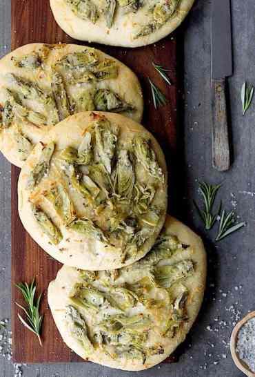 Artichoke Foccacia with Rosemary - Overhead close-up shot of foccacia on wood breadboard