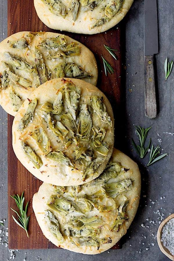 Artichoke Focaccia with Rosemary - Overhead close-up shot of foccacia on wood breadboard