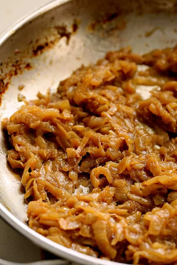 Close-up shot of caramelized onions in stainless steel skillet