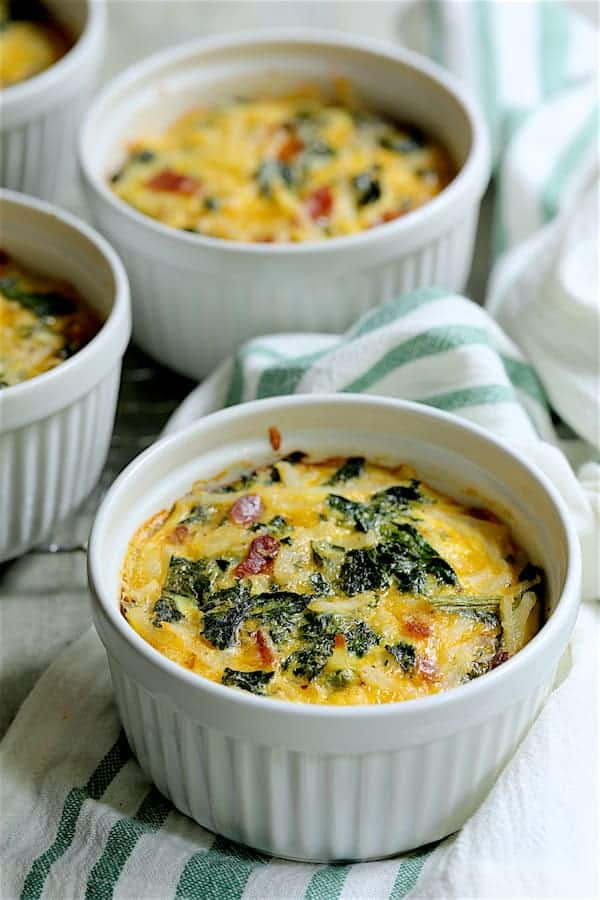 Hash Brown Frittatas with Kale, Bacon and Cheddar - Hero shot on white and green striped towel with three more frittatas in the background