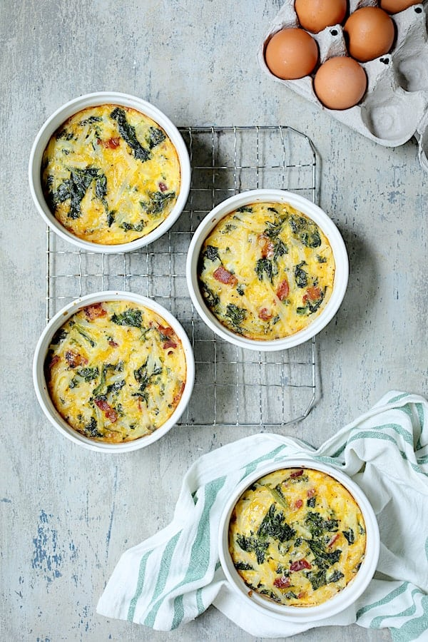 Hash Brown Frittata with Kale, Bacon and Cheddar - Overhead shot of baked frittatas with three on cooling rack and one on green striped towel