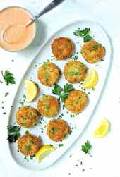 Shrimp Cakes with Roasted Red Bell Pepper Mayonnaise - Overhead hero shot of shrimp cakes on white platter garnished with lemon and parsley