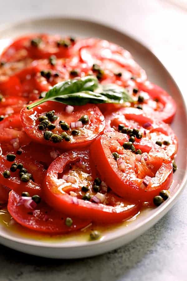 Easy Fresh Tomato Salad - Shot of salad on white platter with capers added