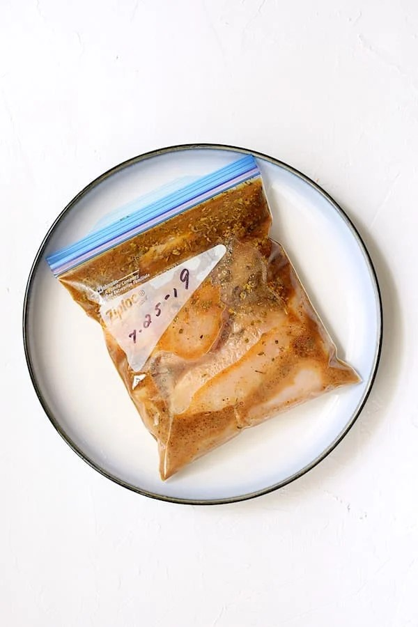 Overhead shot of chicken in marinade in zipper-top bag on plate