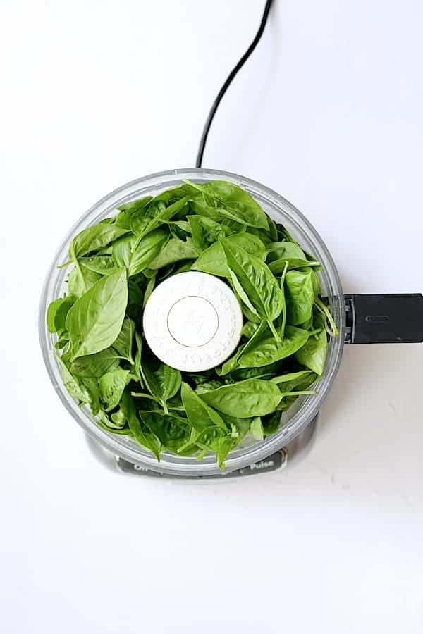 Overhead shot of fresh basil leaves in food processor