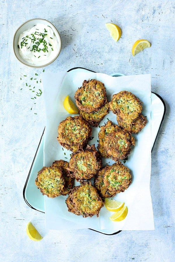 Zucchini Ricotta Fritters - Overhead shot on light blue background with yogurt garnished with chives and lemon