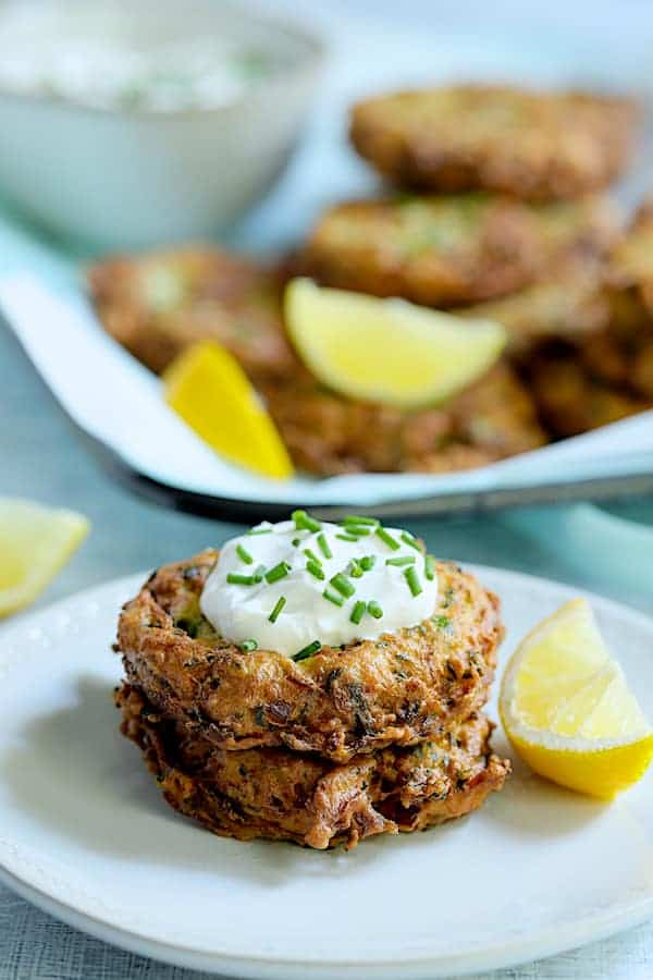 Zucchini Ricotta Fritters - Two fritters stacked on white plate with yogurt on top garnished with fresh chives and lemon wedges