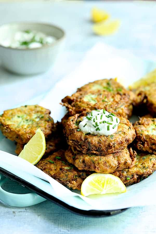 Zucchini Ricotta Fritters - Straight-on shot of fritters on parchment paper-lined serving tray garnished with lemon