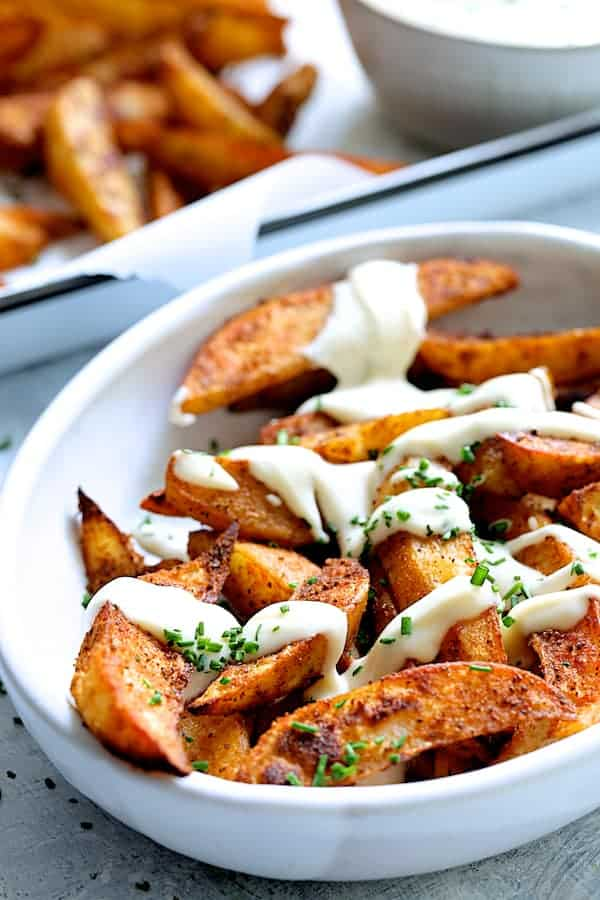 Old Bay Roasted Potato Wedges with Vermont Cheddar Cheese Sauce - Close-up shot of potatoes in white bowl