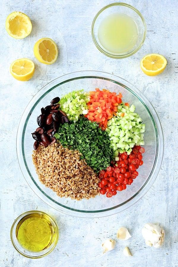 Mediterranean Farro Salad - Overhead shot of salad ingredients in glass mixing bowl