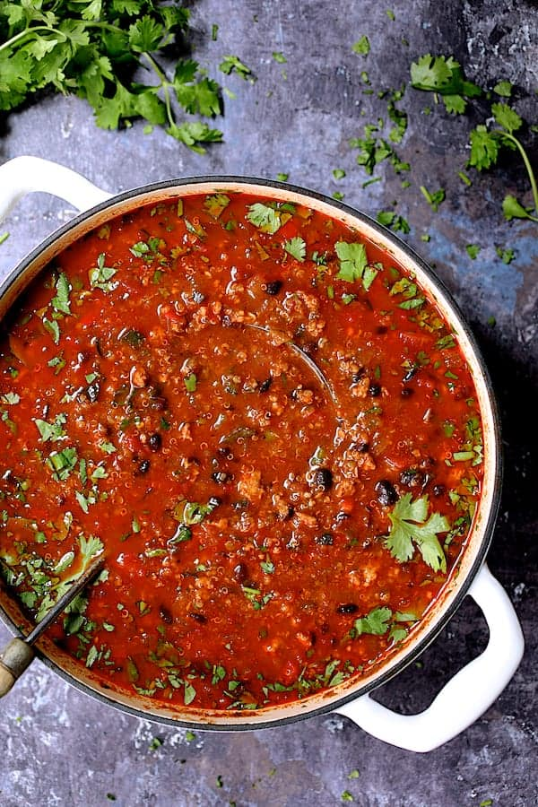 Turkey, Black Bean and Quinoa Chili - Overhead shot of the whole pot of chili in white Dutch oven on gray distressed background garnished with cilantro
