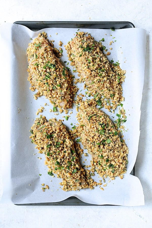 Walnut-Crusted Chicken with Pomegranate Sauce - Overhead shot of chicken breasts coated with walnuts on parchment paper before baking