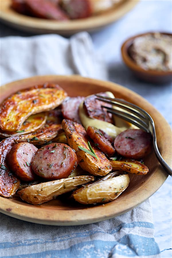Duck Fat Roasted Fingerling with Sausage - Straight-on close-up shot in wooden bowls