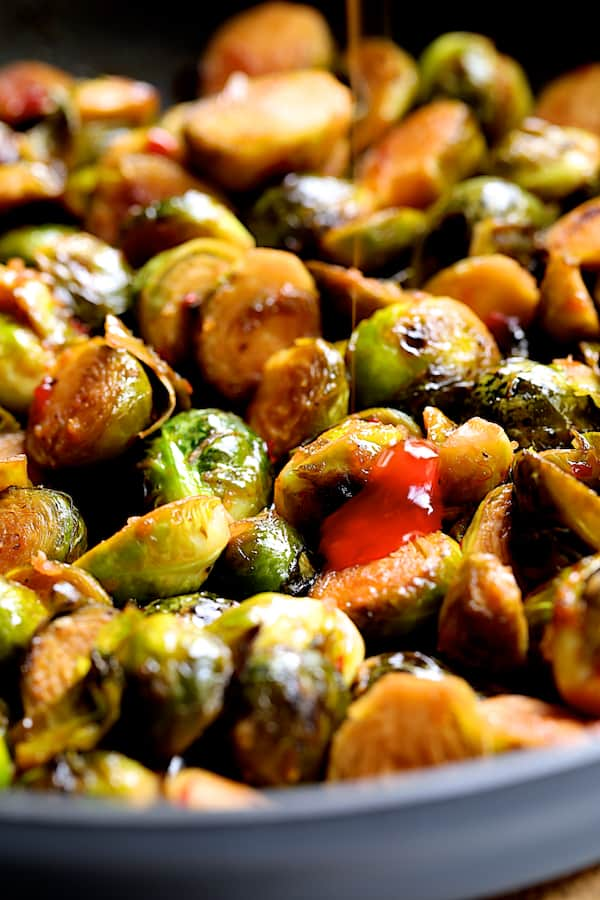 Pan-Roasted Brussels Sprouts with Thai Sweet Chili Orange Glaze - Close-up shot of sprouts in skillet with sweet chili sauce being drizzled over