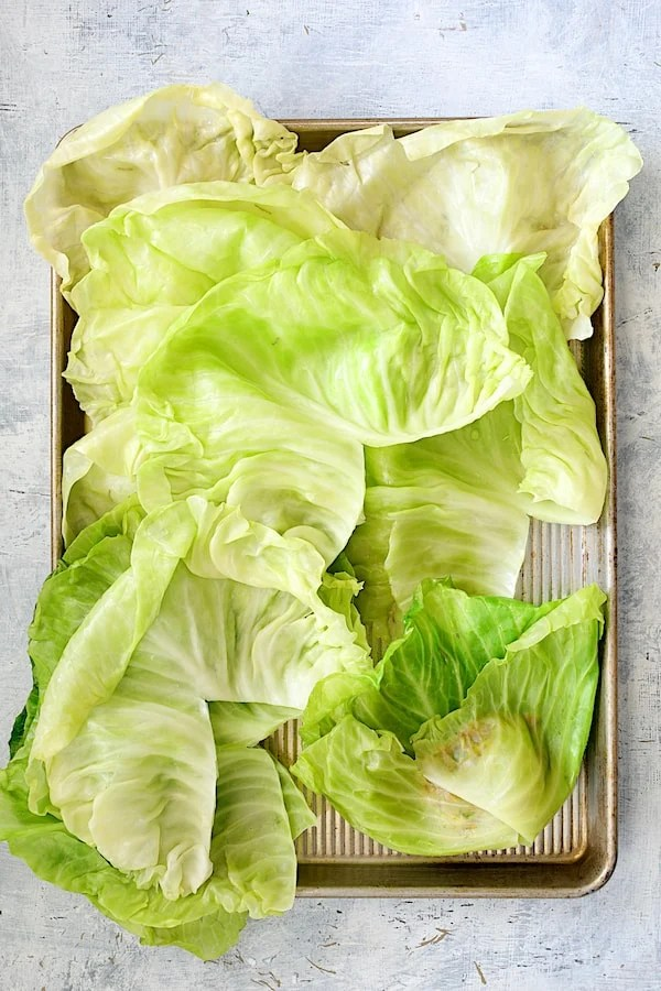 Spicy Italian Stuffed Cabbage - Overhead shot of cabbage leaves with one in the process of being folded and rolled