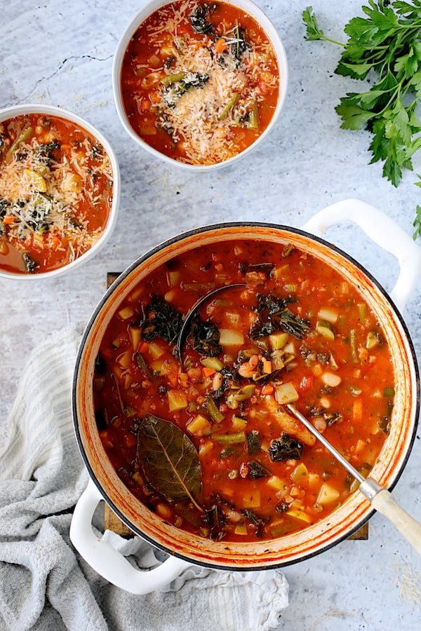 Italian Vegetable Stew - Overhead shot of soup in Dutch oven with it served in two white soup bowls