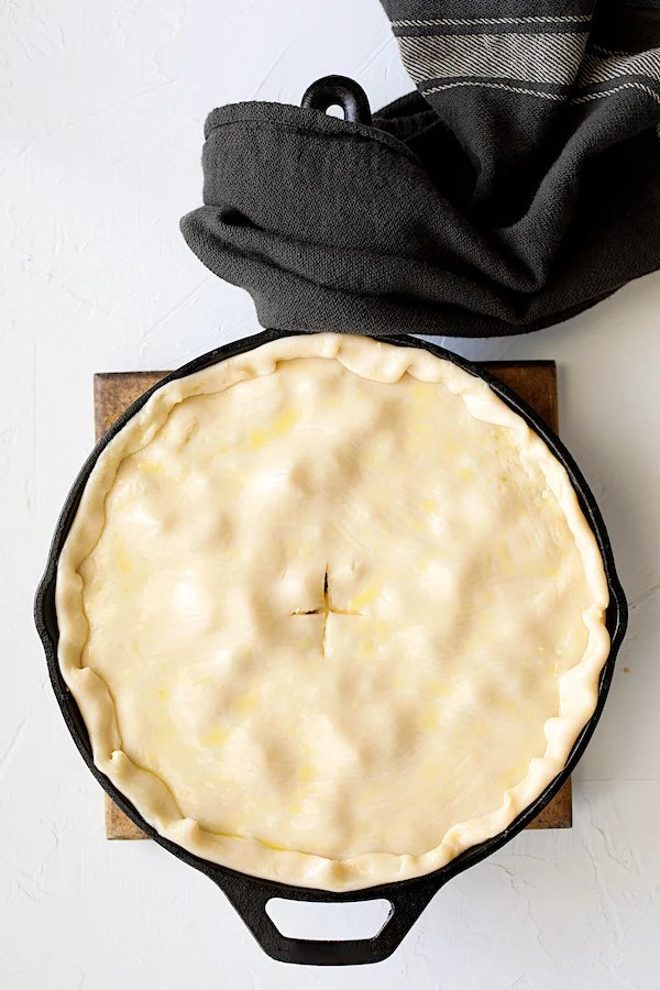 Cheesy Skillet Chicken Pot Pie - Overhead process shot of with pastry placed over pot pie