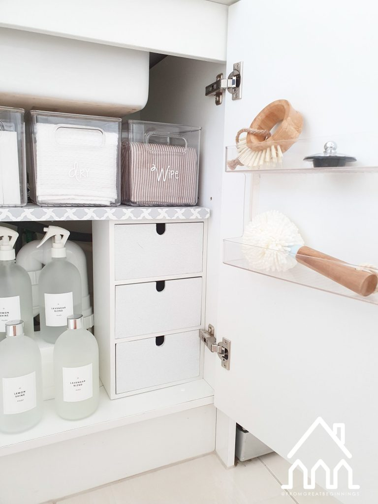 Photo of under the sink organisation including acrylic baskets, DIY shelves enveloped with patterned contact paper, clear spray water bottles used to store cleaning supplies labeled with cricut white labels.