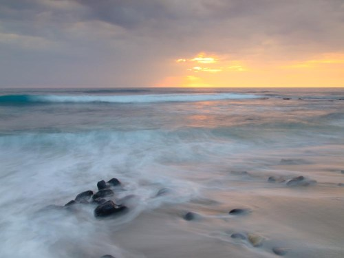 Waves play on the shoreline during a stormy sunset from Honl's beach, Kailua Kona, Hawaii.