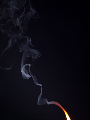 Flame with a ribbon of smoke trailing upwards