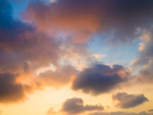 Clouds over Hawaii during a sunset are soft and pastel colored