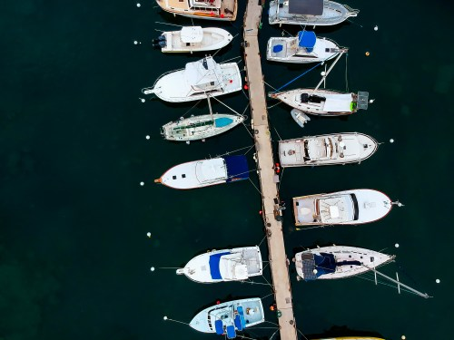 Aerial photograph of motor boats and sail boats tied off onto a wooden dock at Honokohou harbor on the Big Island of Hawaii
