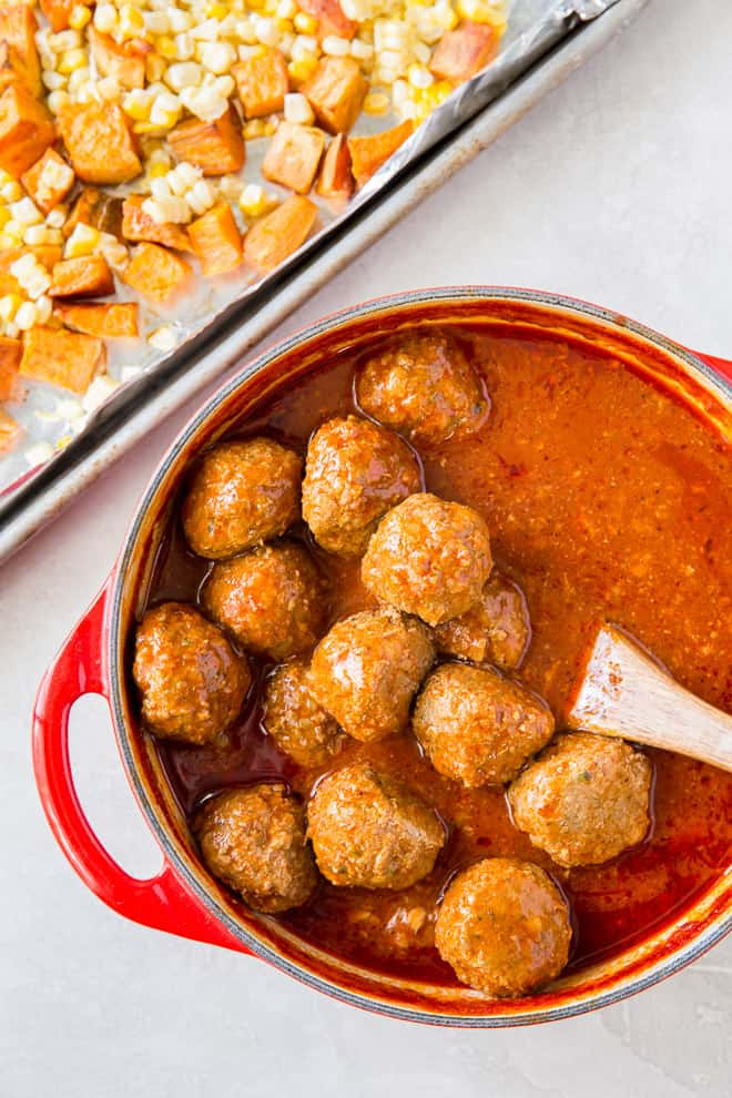 Meatballs in sauce in a dutch oven with a wooden spoon.