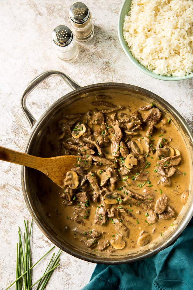 Beef Stroganoof in a pan with a bowl of rice and salt and pepper shakers behind it.