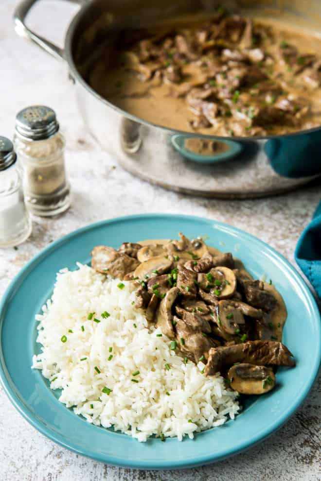 A blue serving plate with rice and Beef Stroganoff.