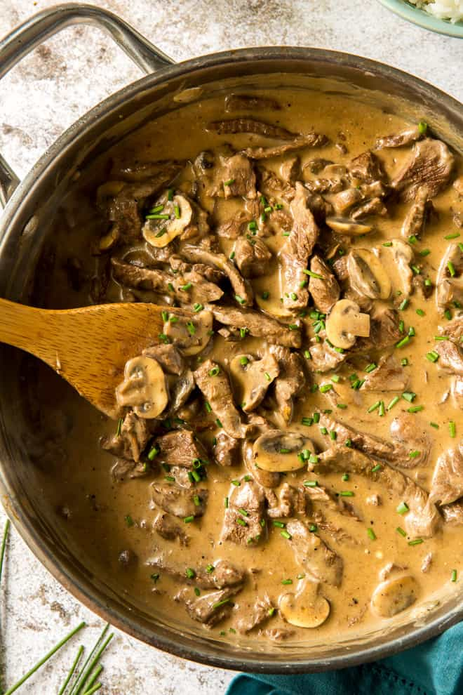 A close up image of the Beef Stroganoff in a pan with a wooden spoon.