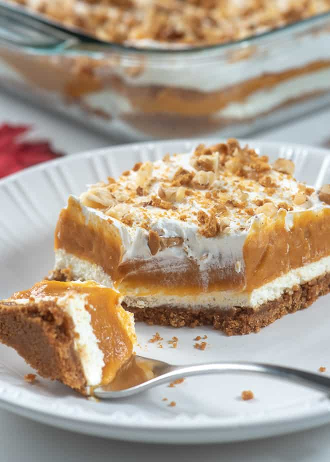 A fork breaking into a slice of Creamy Layered Pumpkin Dessert.