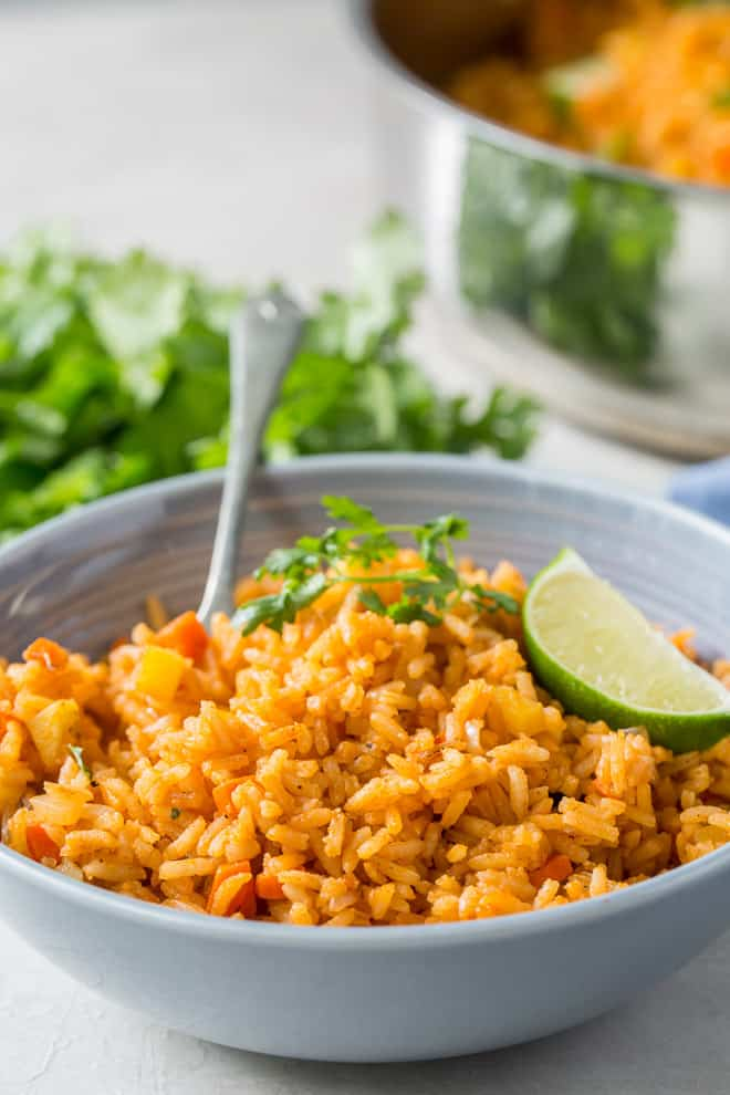 A serving of Restaurant Style Mexican Rice in a serving bowl with a fork.