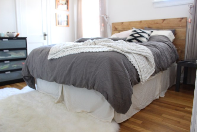 Cozy neutral bedroom, gray linen bedding, cableknit blanket, sheepskin rug