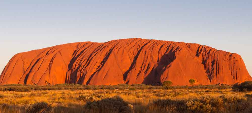 Explore the Australian Outback + see gorgeous natural wonders, like Ayer's Rock.