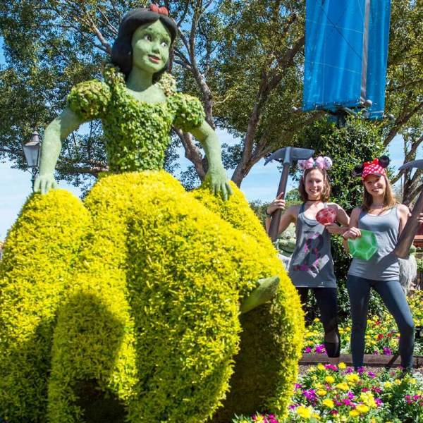 Photo of a Snow White Topiary at Epcot, with 2 young women posing for a picture.