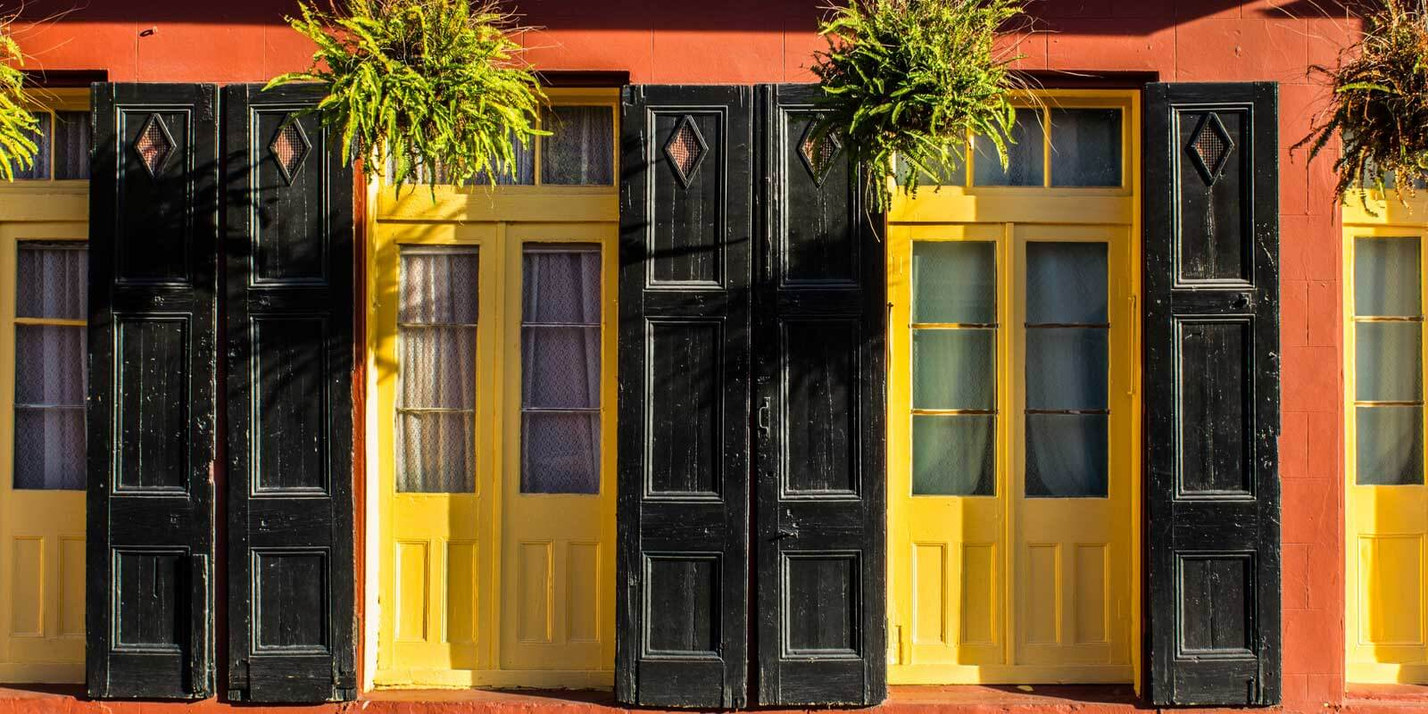 Close up of an orange building with bright yellow doors, black shutters, and lush hanging plants.