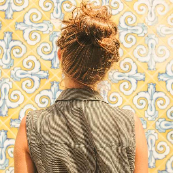 Woman looking at yellow, white and blue Spanish tiles on a wall.