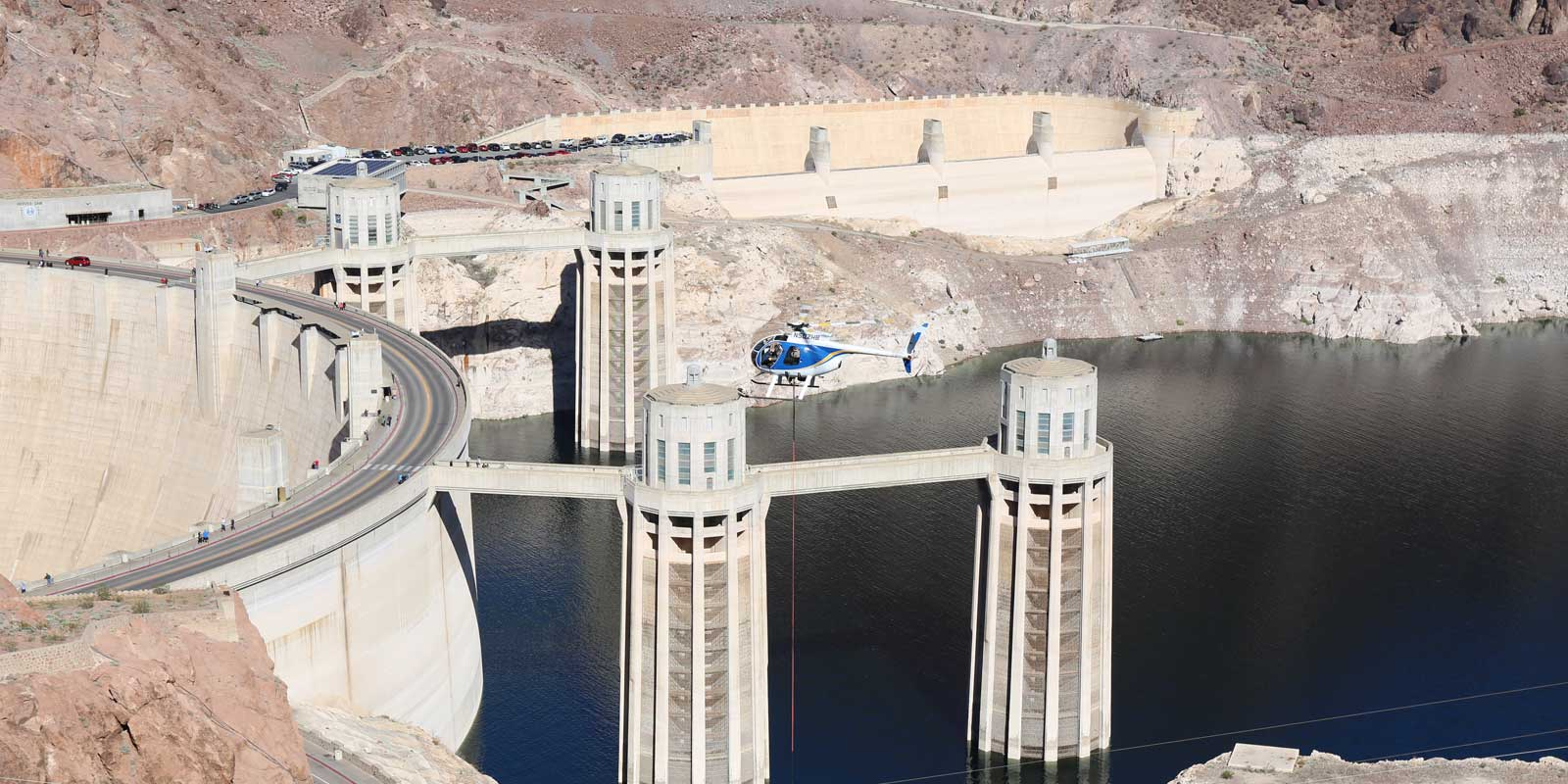 Photo of a helicopter hovering over the Hoover Dam Intake Tower Bridge.