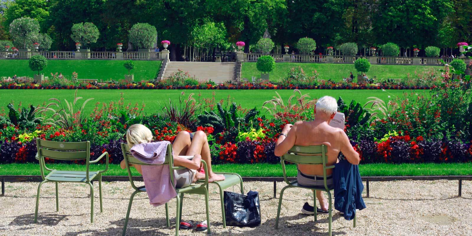 Woman and man enjoying a warm day in Le Jardin du Luxembourg in Paris.