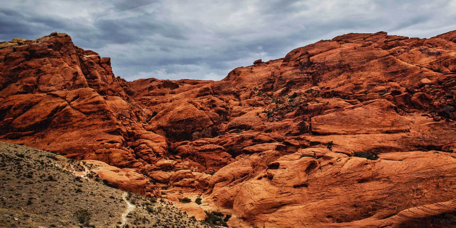 Landscape photo of rusty red rock formations set against a cloudy sky.