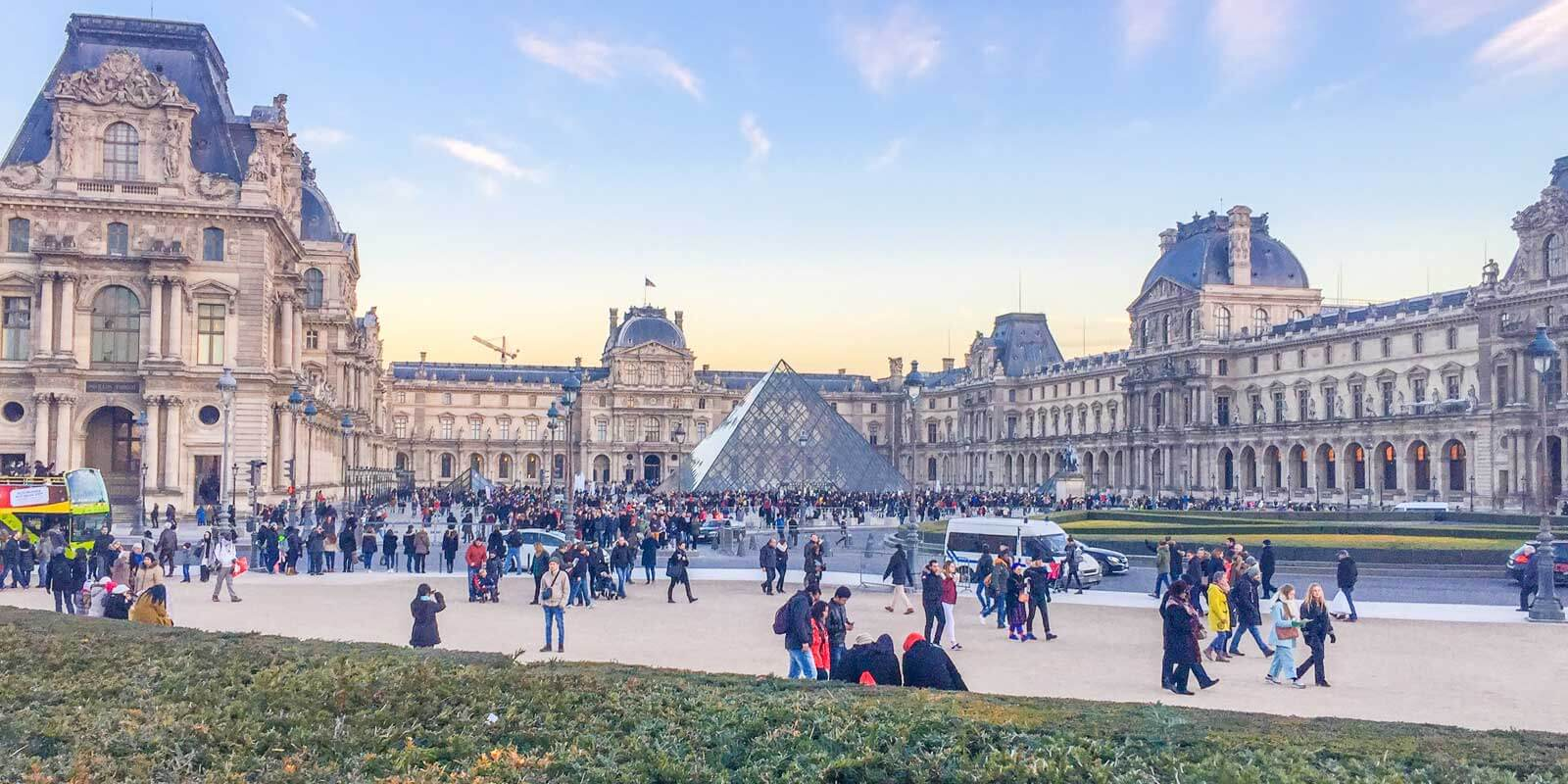 Crowds walking outside the front entrance to The Louvre at sunset.