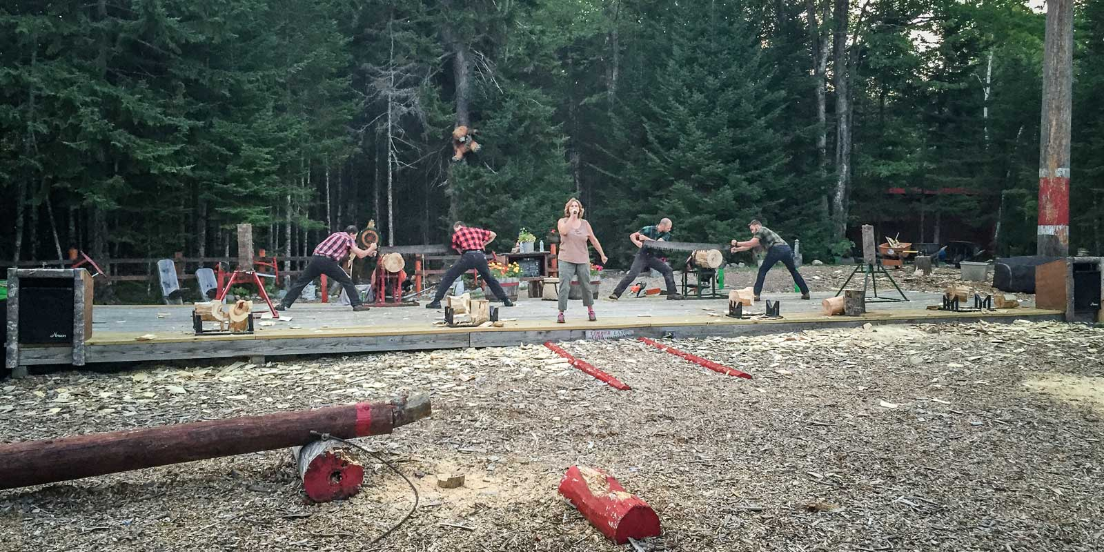 Two teams of lumberjacks compete at hand-sawing a log.