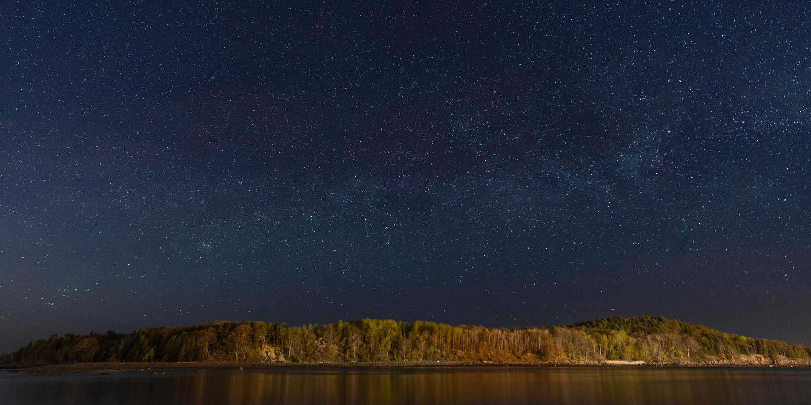 Landscape image of stars in the night sky in Bar Harbor, Maine.