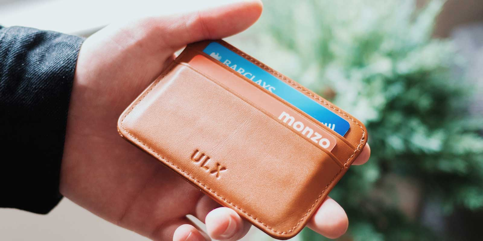 Man holding a small brown wallet with 2 credit cards in it.