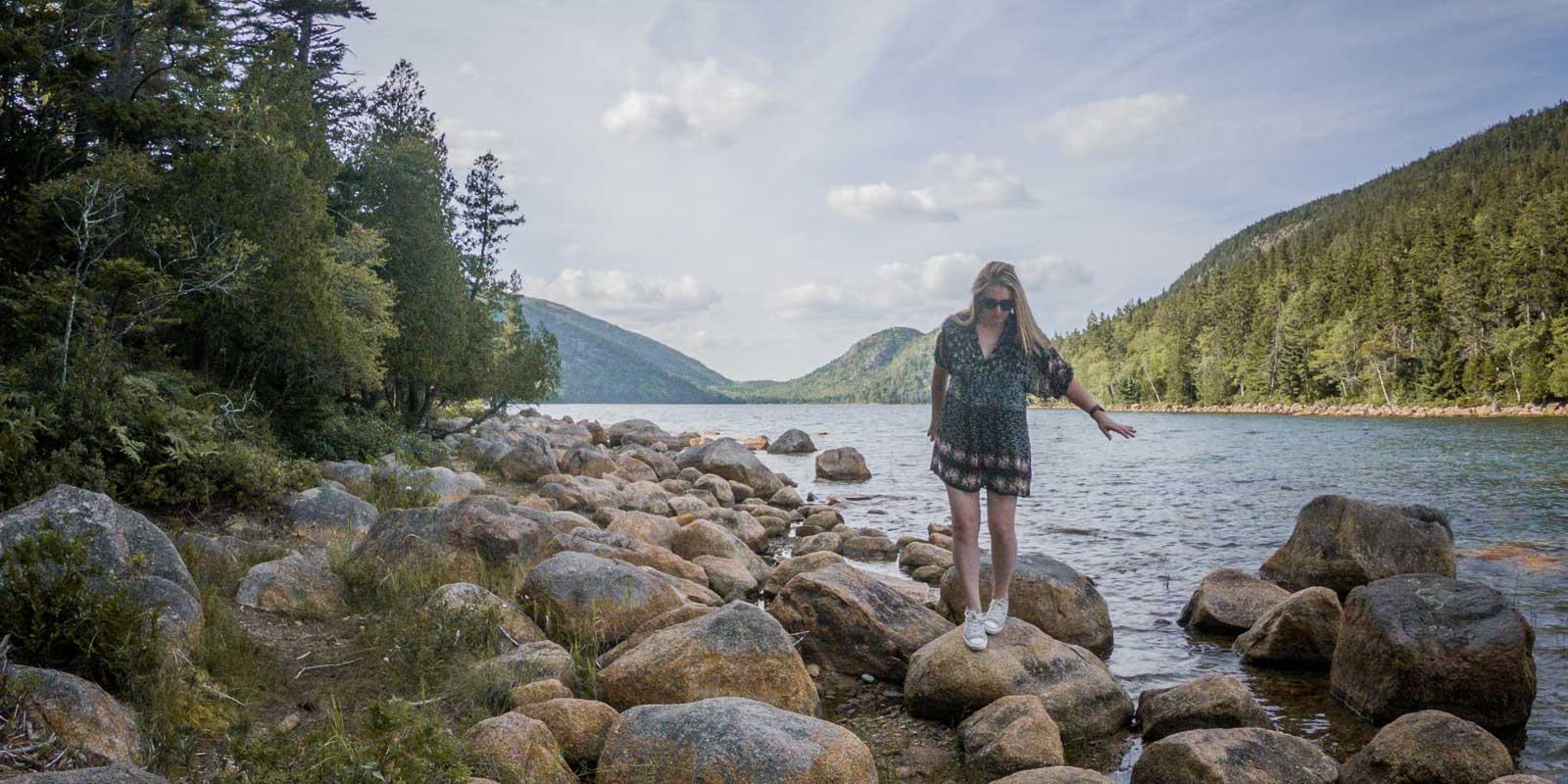 Travel blogger Meg Frost walking across rocks on the shore of Jordan Pond, while hiking the Jordan Pond trail loop in Acadia National Park, Bar Harbor, Maine.
