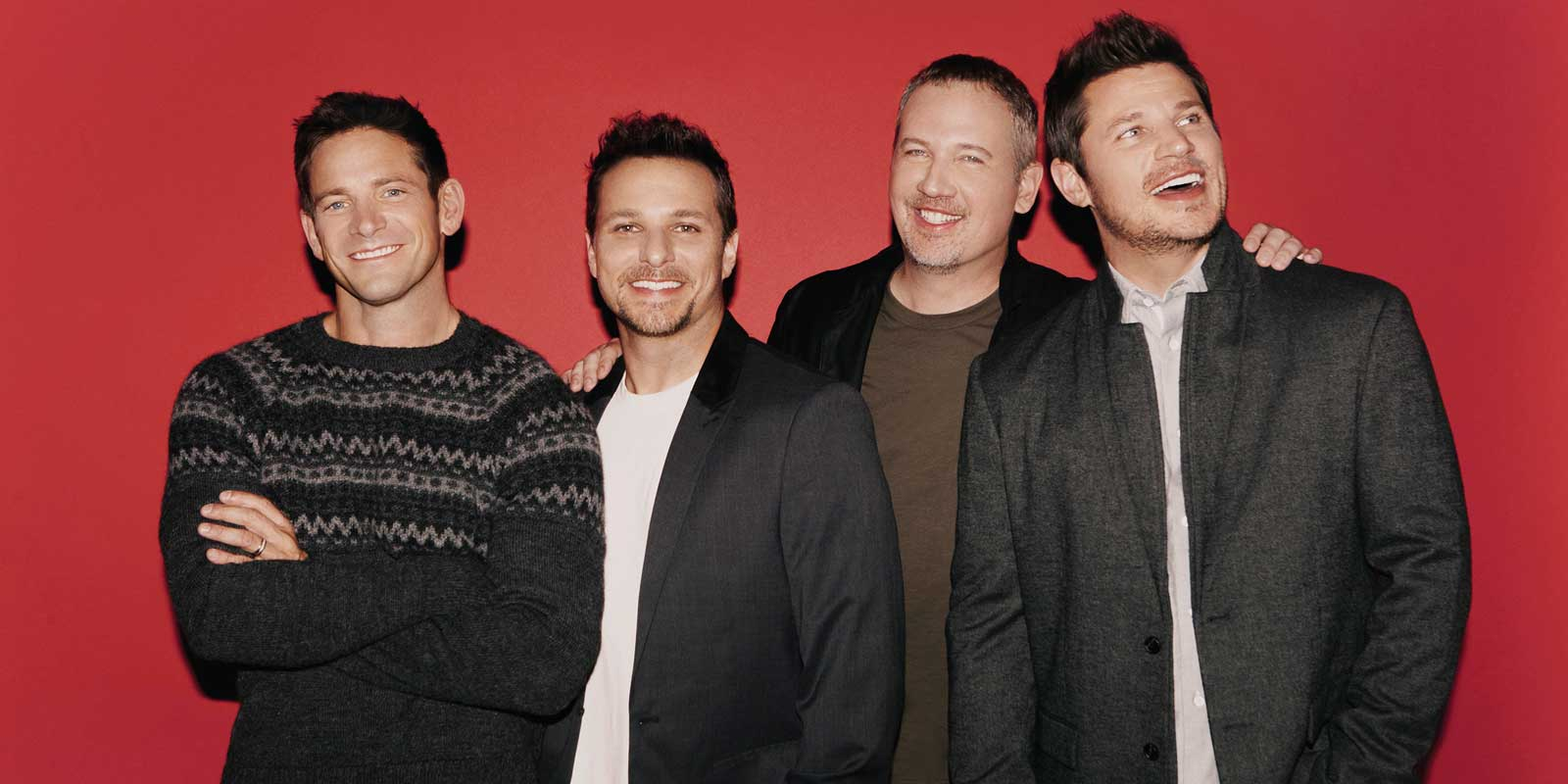 The 90s boys band 98 Degrees poses in front of a solid red background.