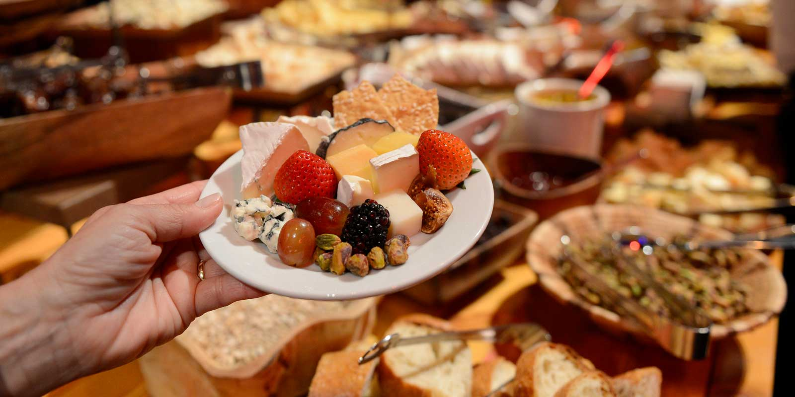 Close up of a small plate filled with various cheeses, fruit, and nuts at the Epcot Party for the Senses.
